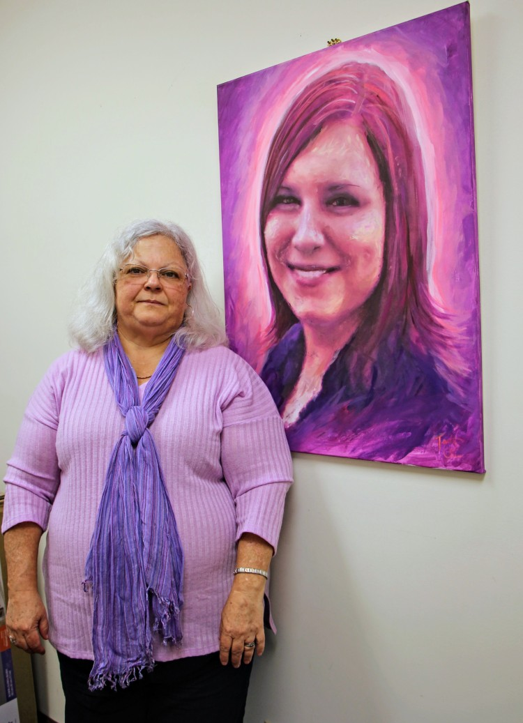 Susan Bro stands next to a portrait of her daughter 2